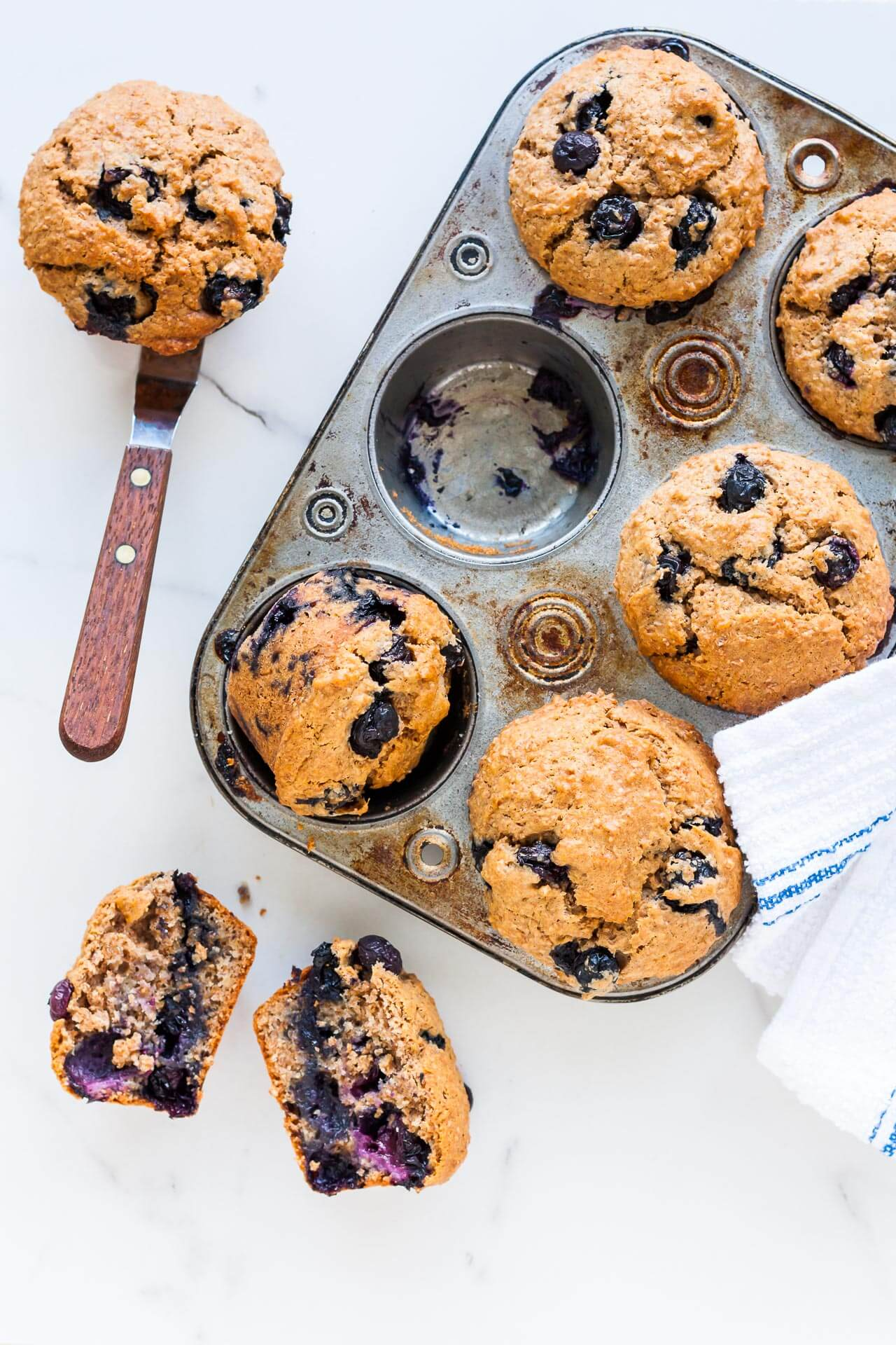 Vintage muffin pan with baked blueberry bran muffins. One cup empty and muffin is on side on an offset spatula. One muffin is broken open to show moist interior of muffin