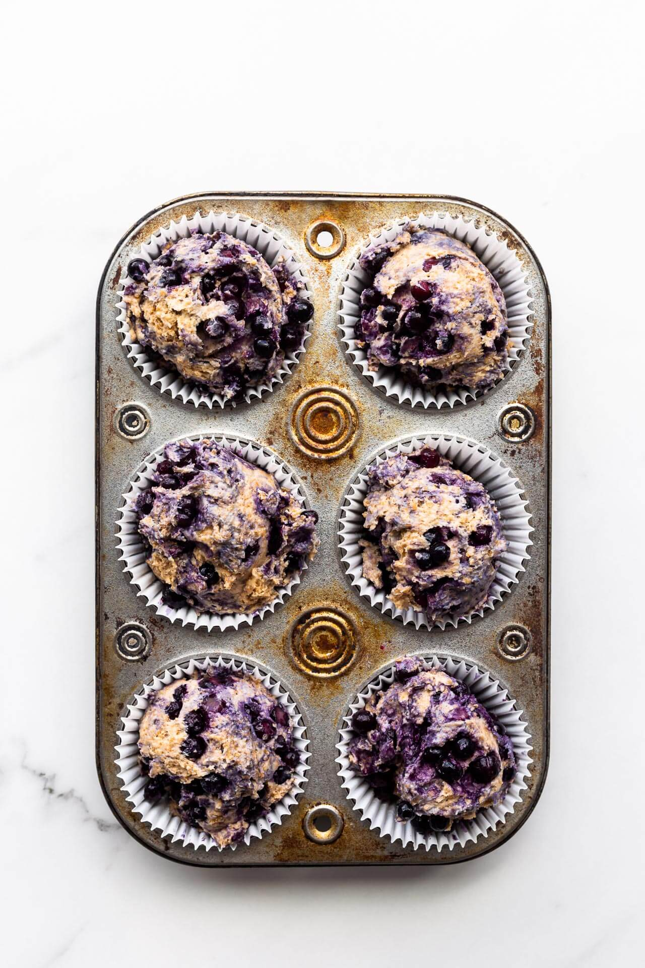 Blueberry bran muffins divided between paper liners in a vintage muffin pan