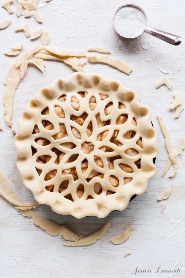 Double crust apple pie unbaked and ready for the oven, featuring intricate design on top crust of floral cut-out pattern