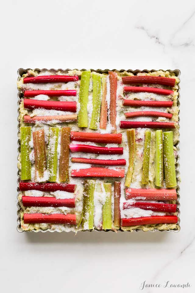 Rhubarb cake before baking to show how rhubarb is arranged in a pattern like it's woven