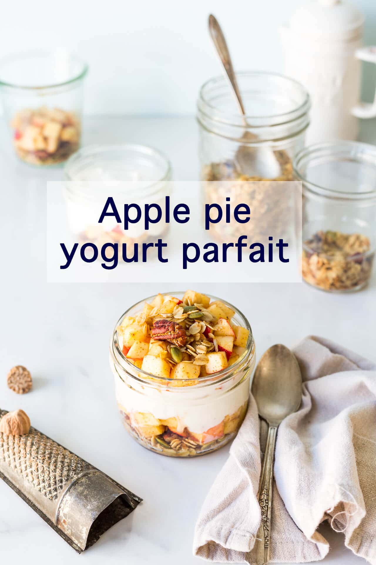 Apple pie parfait made in a jar with layers of yogurt, spiced diced fresh apple, and granola, eaten with a spoon and served with freshly grated nutmeg
