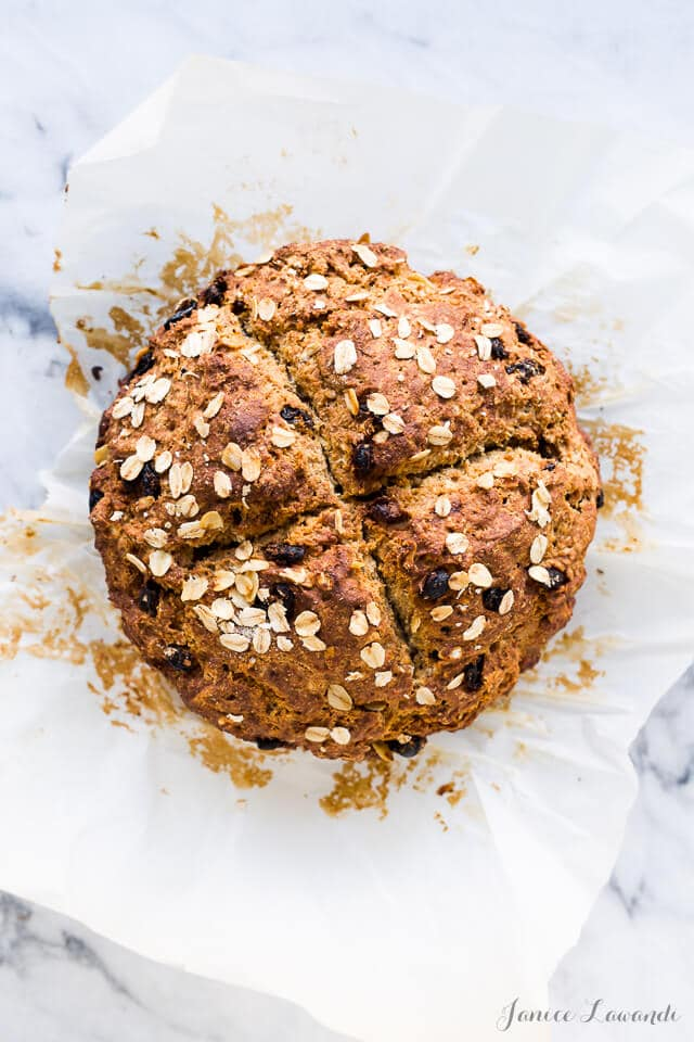 A golden brown loaf of Irish soda bread with raisins topped with oats and scored with an X