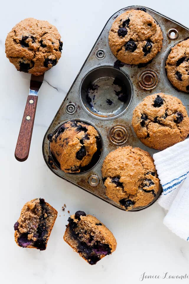 A muffin pan of blueberry bran muffins with 1 cup empty. One muffin on an offset spatula and another muffin broken open to reveal the interior