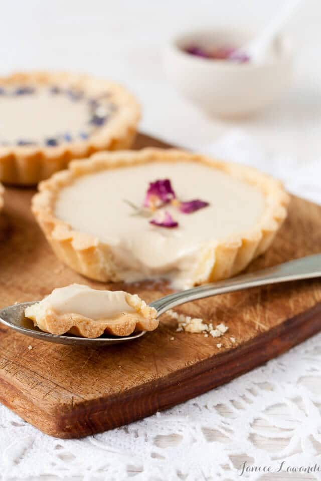 Little Earl Grey panna cotta tarts decorated with dried rose petals and dried cornflower, cut into with a spoon