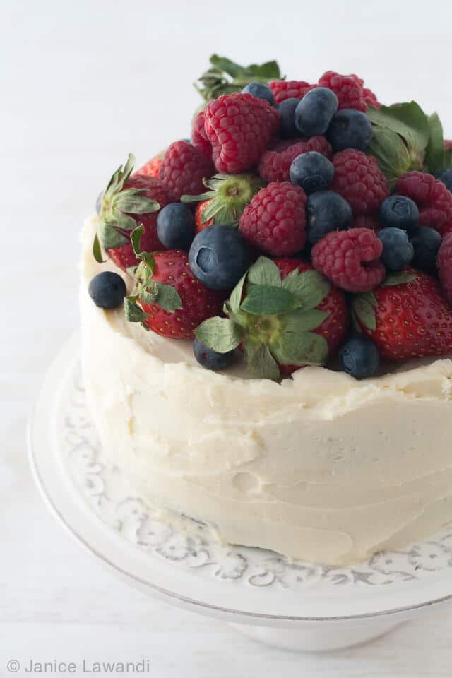 Layer cake with cream cheese frosting (creamy white colour) topped with a pile of fresh berries on a cake stand