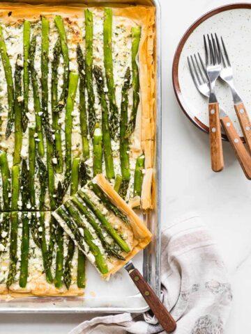 Asparagus phyllo tart with ricotta, feta, herbs, and lemon zest, cut into slabs