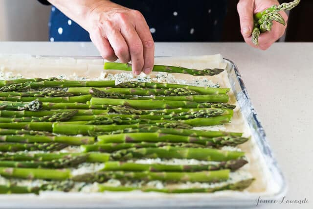 Building an asparagus phyllo tart with ricotta, feta, herbs, and lemon zest