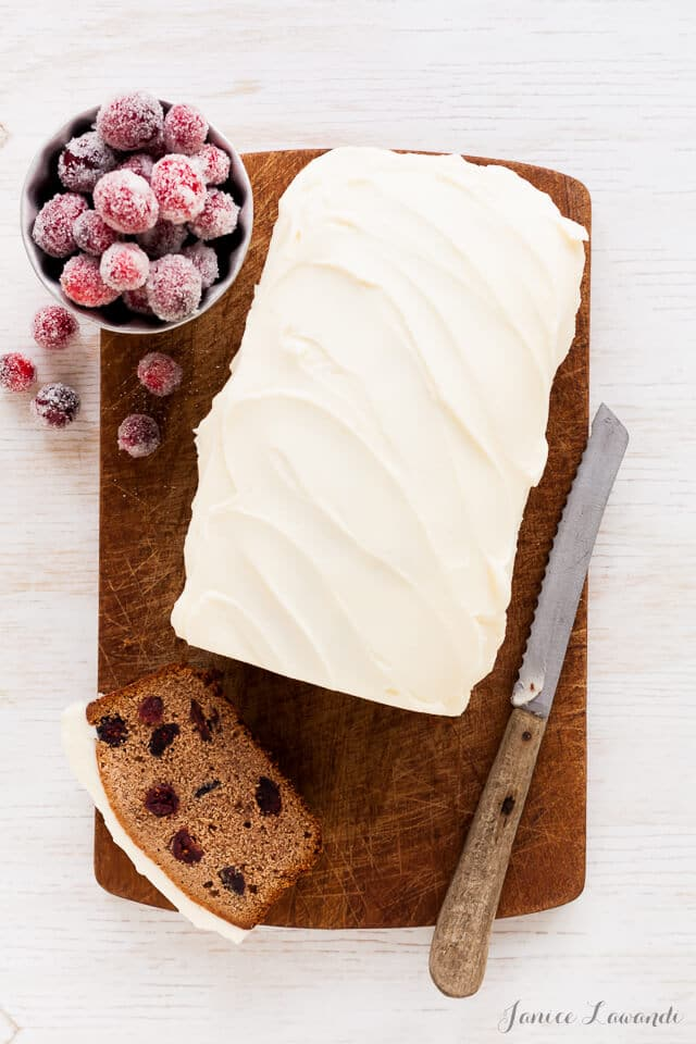 Frosted cranberry chestnut loaf cake sliced on a wood cutting board with a serrated knife and served with a bowl of sugared cranberries