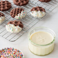 Dipping chocolate cookies in white chocolate and sprinkles