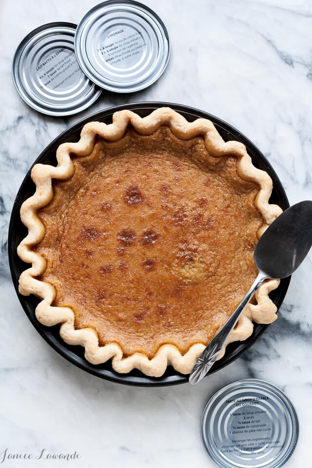 Maple syrup custard pie baked in a dark metal pie pan with pie server