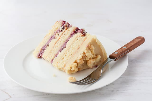 Slice of Momofuku Milk Bar style cake-layers of blackberry curd, almond cake, and almond frosting