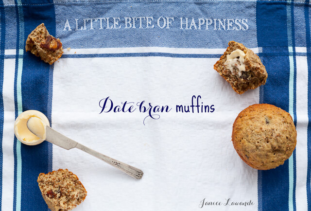 """Date bran muffins served with butter and butter knife on a tea towel with blue plaid print and """"A little bite of happiness"""" text printed on towel"""