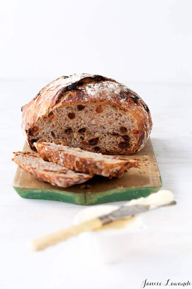 homemade cinnamon raisin bread sliced on a wood cutting board and served with butter and a butter knife