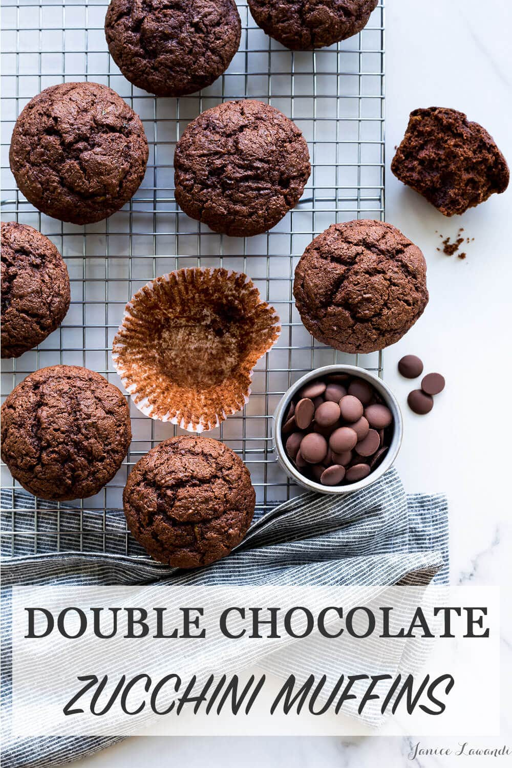 Freshly baked homemade chocolate zucchini muffins on a cooling rack with paper liners and milk chocolate chunks, striped linen