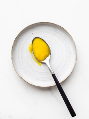A spoonful of bright yellow homemade lemon curd on a ceramic plate.