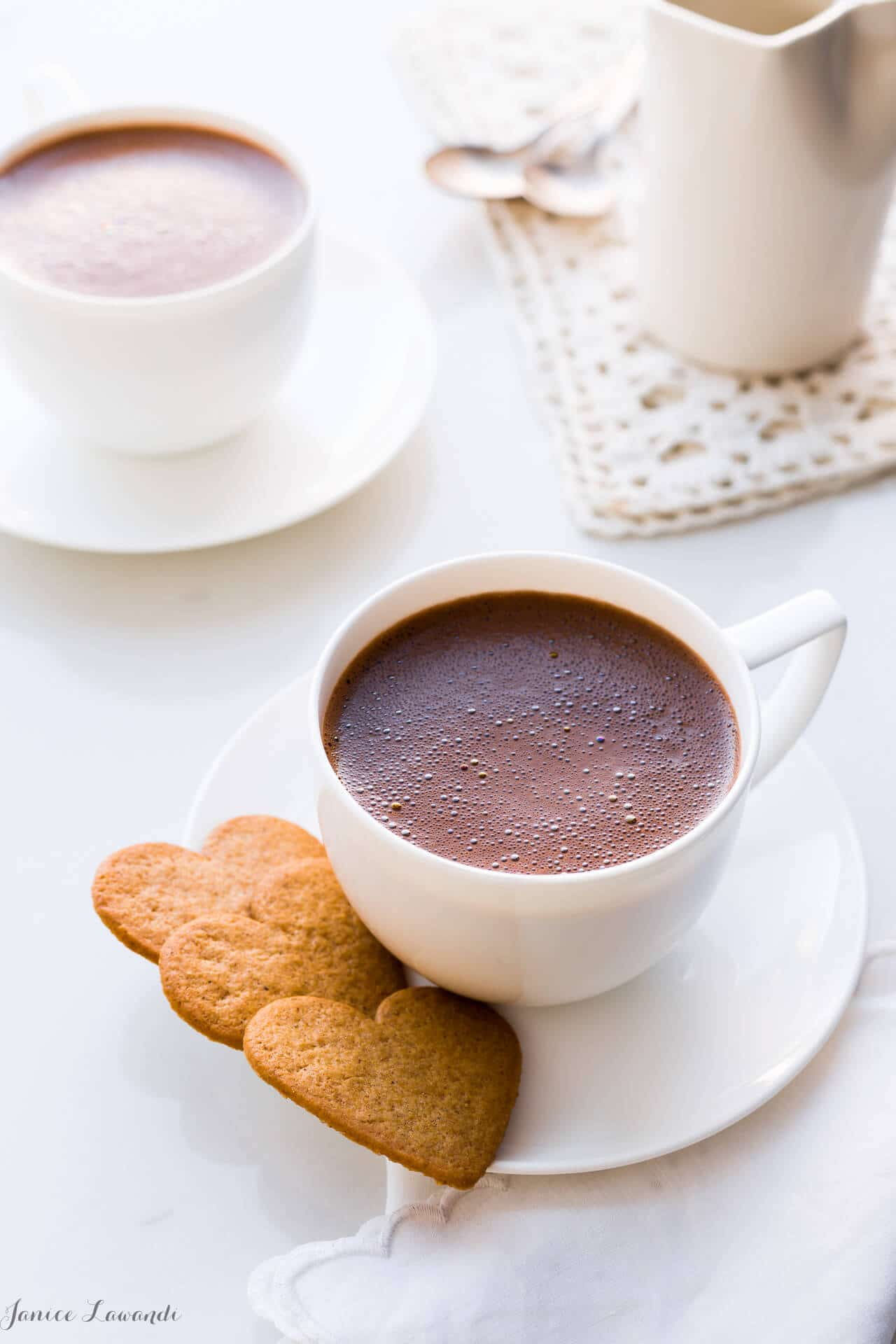 Homemade hot chocolate served in white cups, white saucers, and heart-shaped cookies.