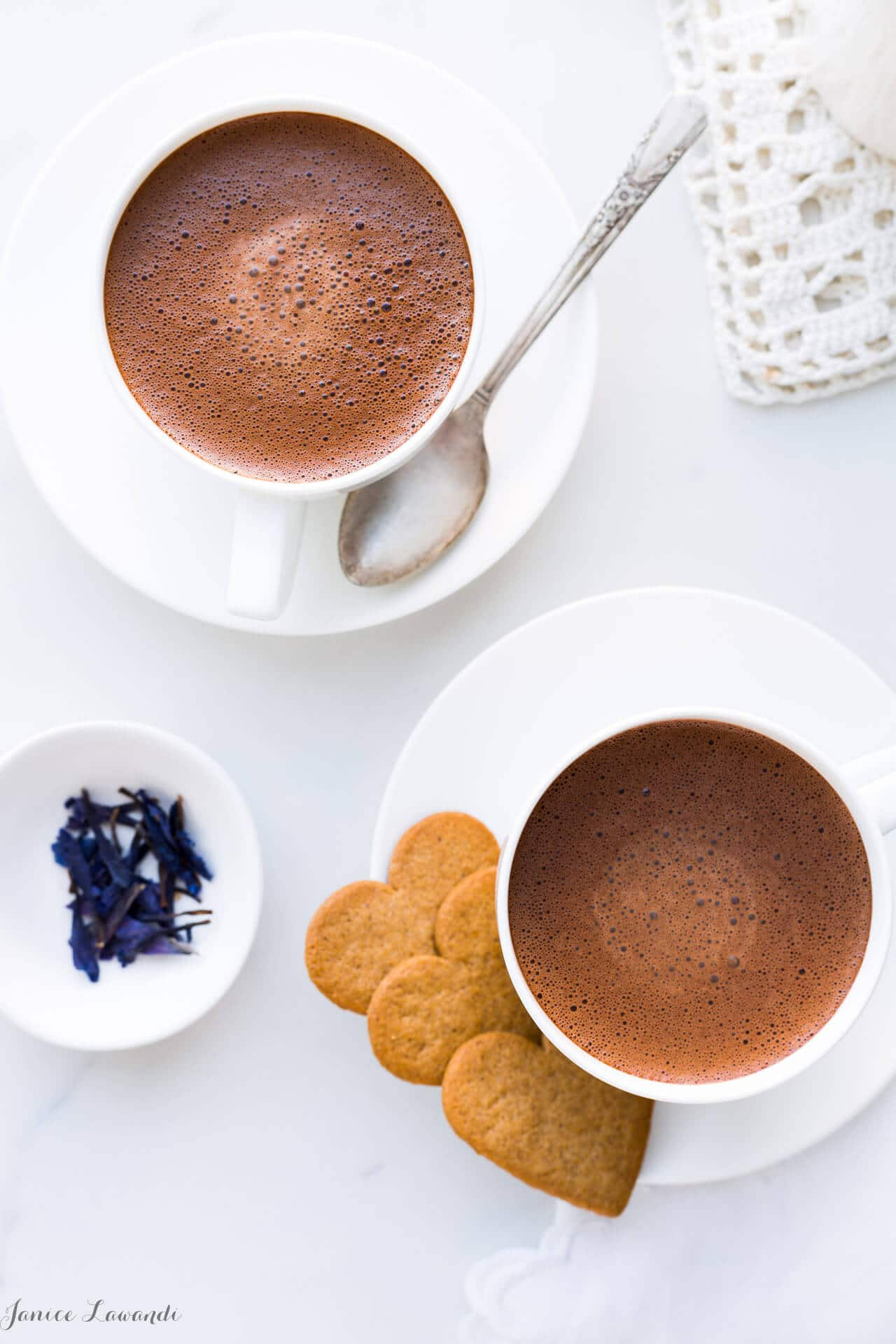 Overhead shot of two cups of hoomemade hot chocolate made with just 2 ingredients: chocolate and milk, and served with heart-shaped cookies.