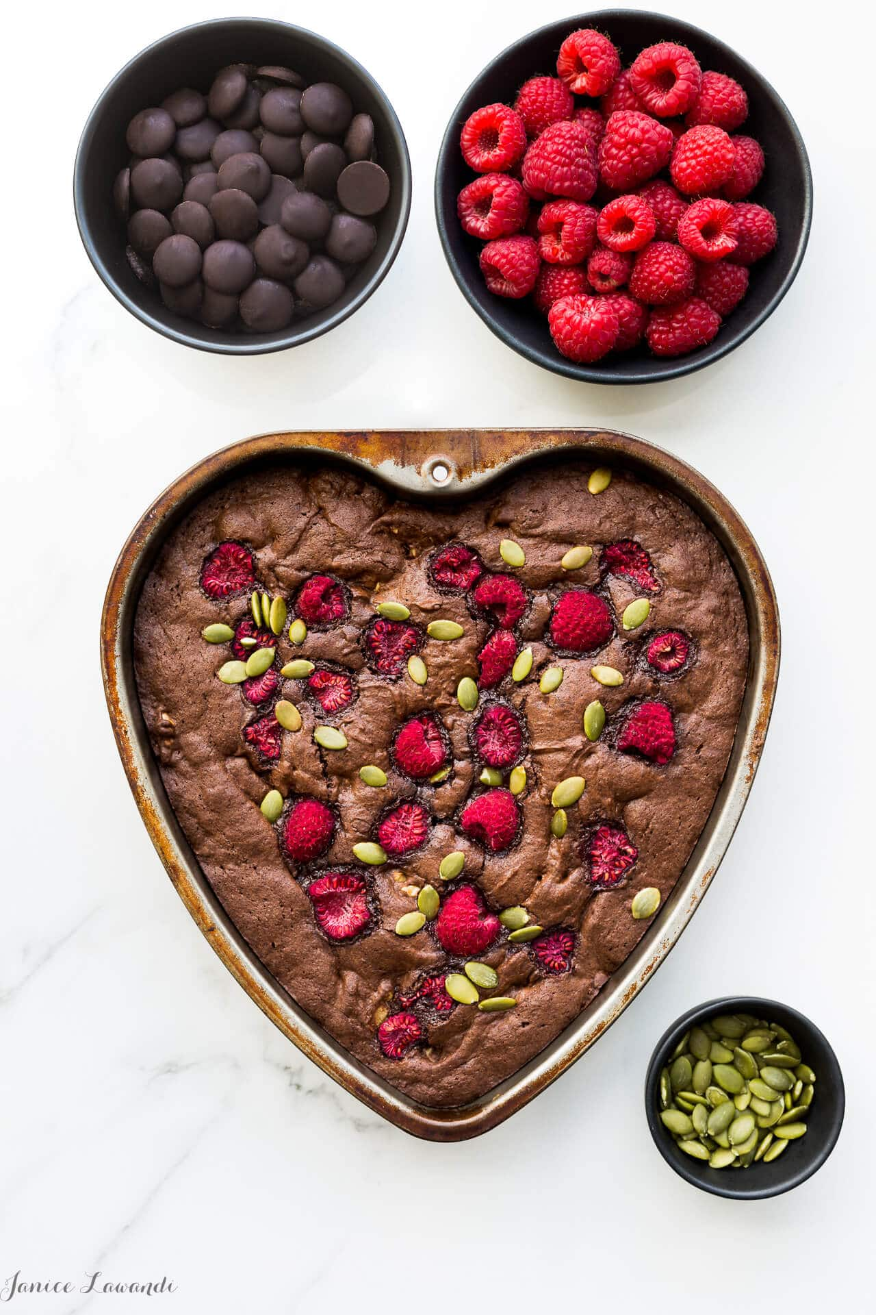 Brownies baked with walnuts and topped with raspberries and pumpkin seeds and baked in a heart shaped pan