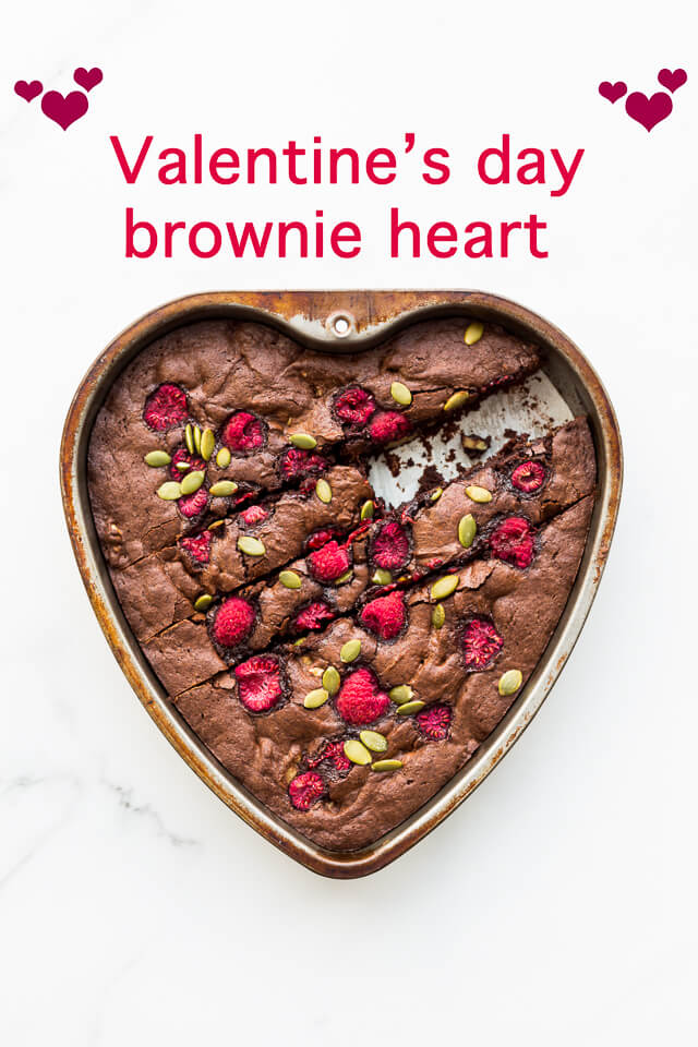 Heart-shaped dark chocolate brownie in a heart-shaped cake pan topped with raspberries and chopped nuts or pumpkin seeds