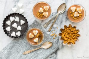Stovetop chocolate pots de crème just like s'mores with a graham cracker cookie crumb crust and toasted marshmallows on top