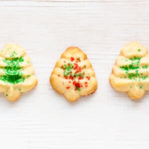 Christmas cookies shaped like christmas trees with green and red sprinkles