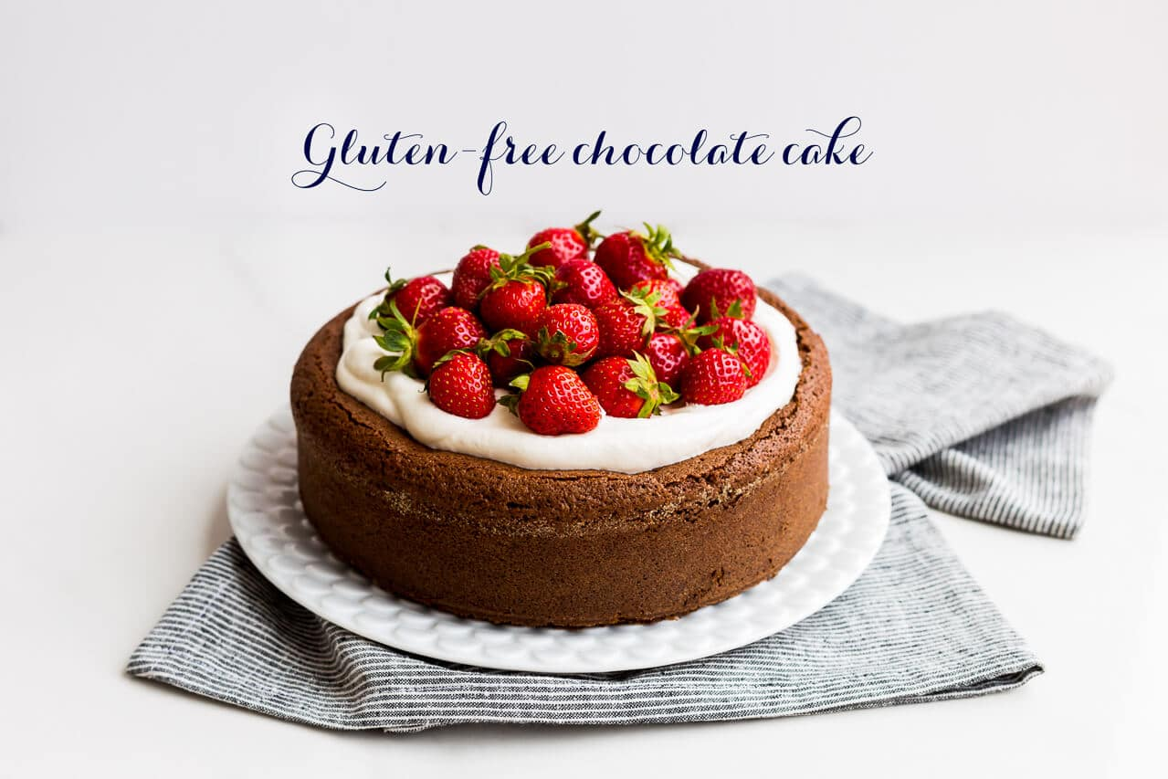 Moist gluten-free chocolate cake with buckwheat flour and ground almond topped with whipped cream and fresh strawberries