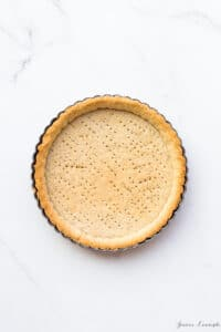 Blind baked sablé cookie crust with fork marks for venting steam