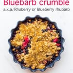 Blueberry rhubarb crumble with a marzipan oat crumble topping served in a round ceramic blue baking dish with a fluted edge