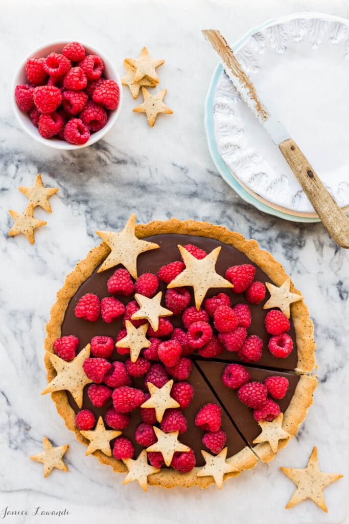 Milk chocolate ganache tart made with a coffee cookie crust and topped with fresh raspberries and cookie stars