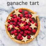 Milk chocolate ganache tart made with a coffee cookie crust and topped with raspberries and cookie stars