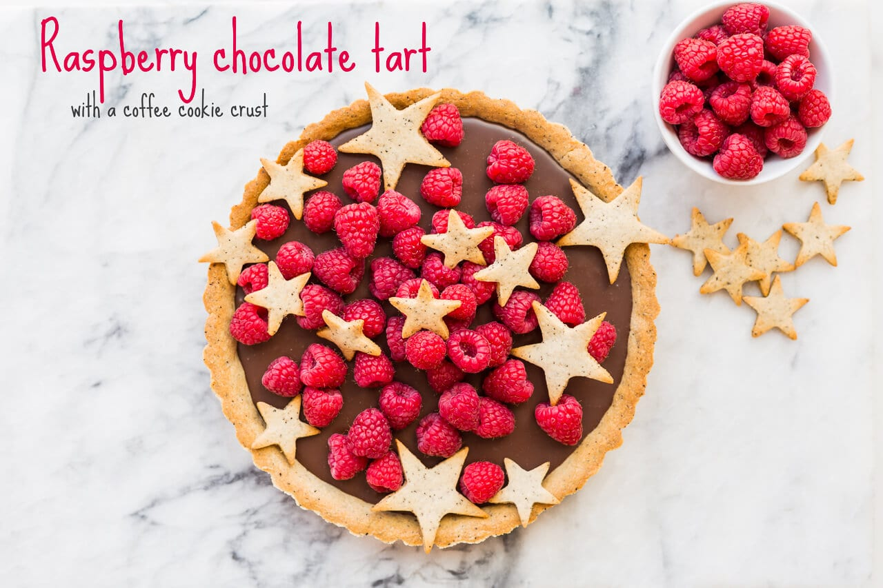 Raspberry chocolate tart with a coffee cookie crust and milk chocolate ganache filling. The chocolate tart is decorated with fresh raspberries and star-shaped cookies