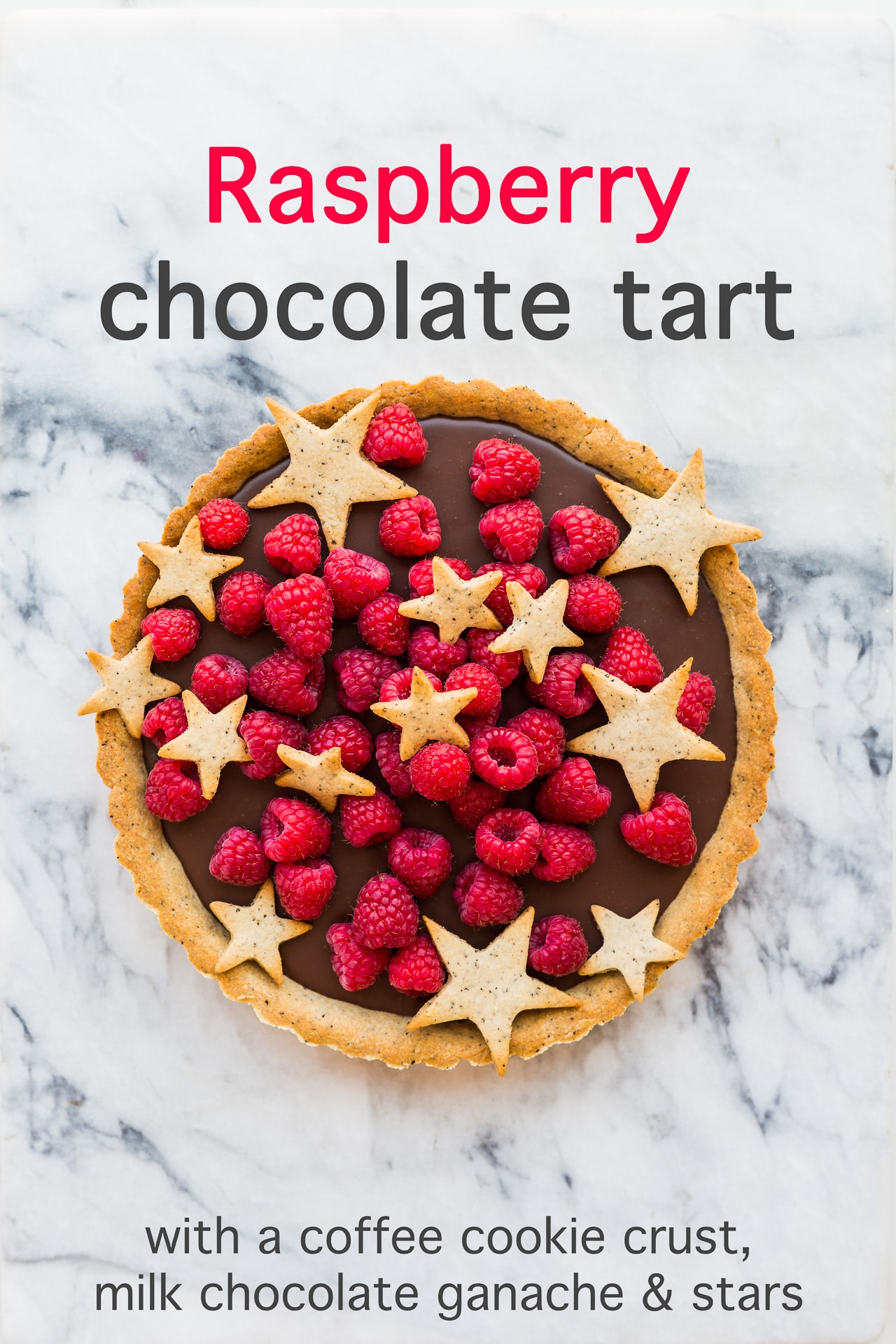 Raspberry chocolate tart with a milk chocolate ganache filling and a coffee cookie crust, decorated with fresh raspberries and star-shaped cookies
