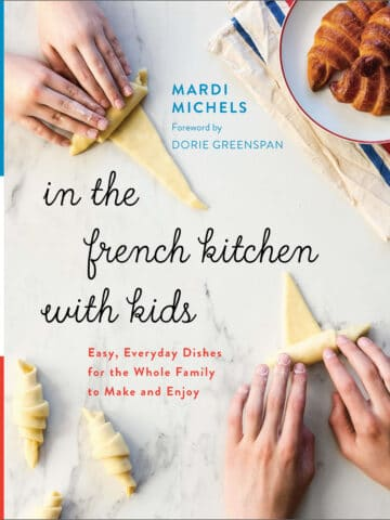In The French Kitchen With Kids by Mardi Michels book cover featuring kids rolling homemade croissants