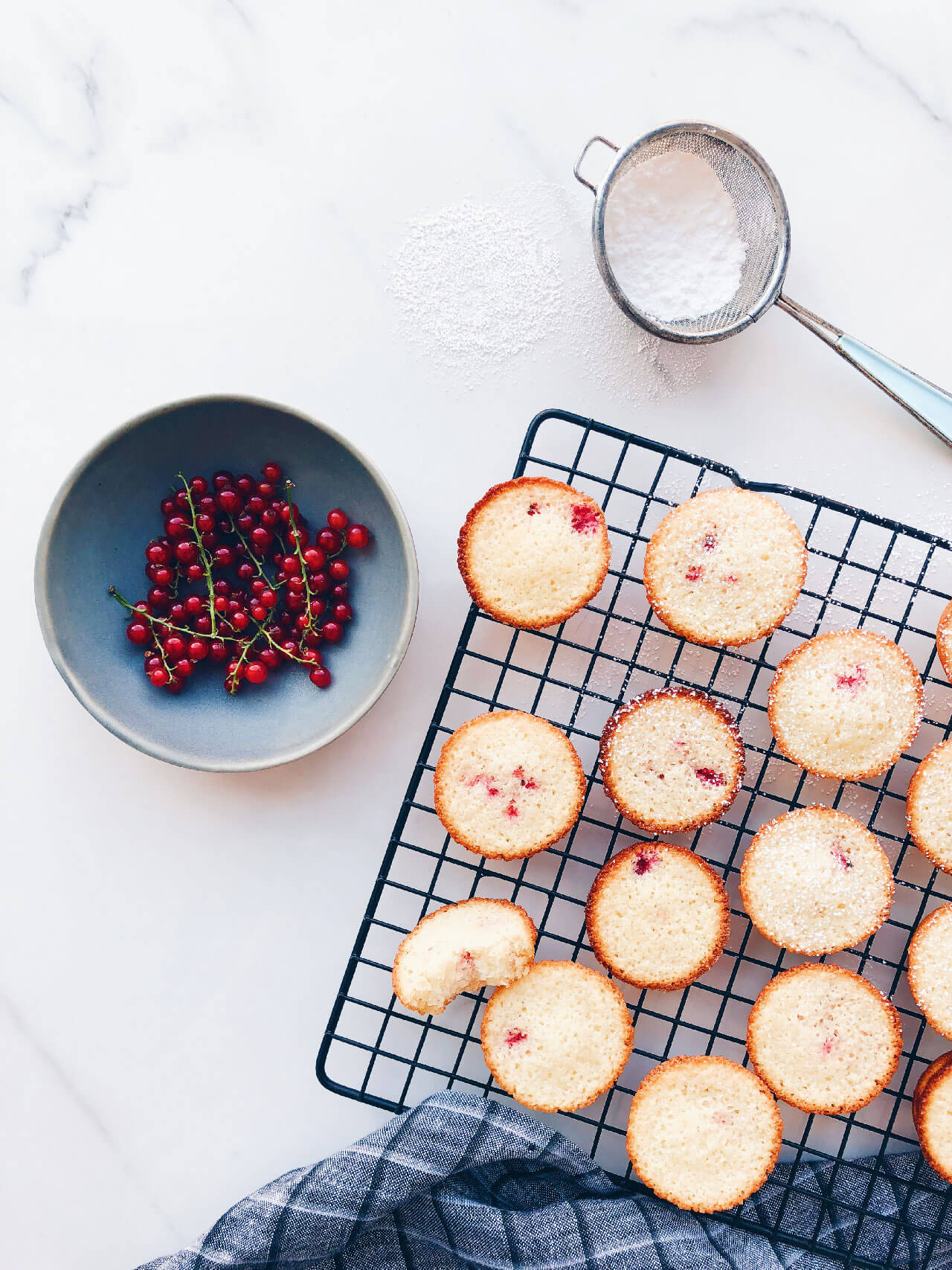 red currant financiers with a bowl of red currants and icing sugar in a small strainer for dusting over the little cakes on a black cooling rack