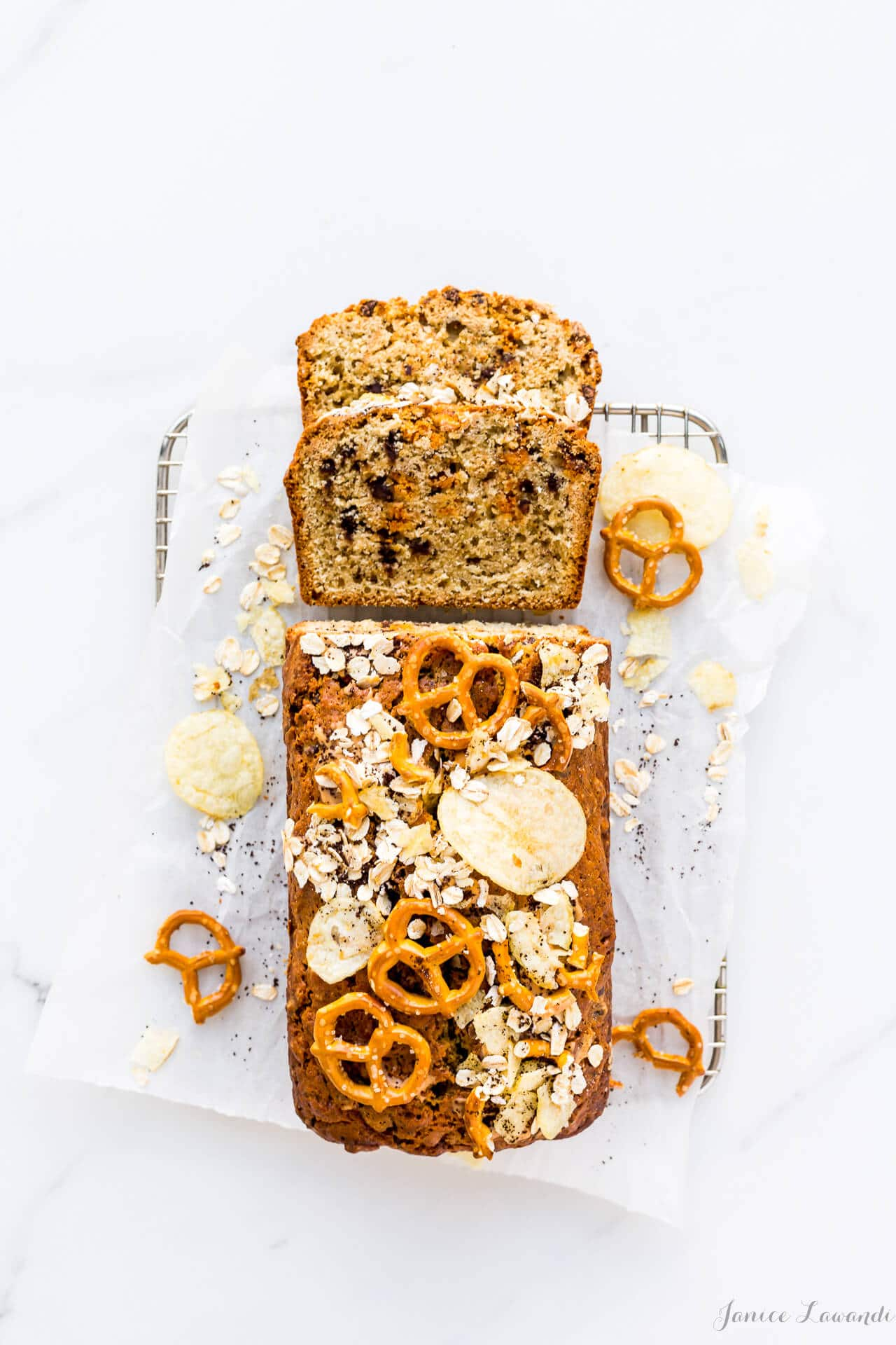 Sliced loaf cake of Christina Tosi's compost pound cake rectangular loaf cake with potato chips, pretzels, chocolate chips, butterscotch chips, oats, and coffee, on a small cooling rack on parchment paper