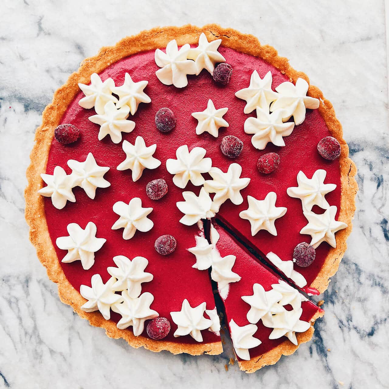 Cranberry curd tart with press-in shortbread crust baked in a fluted tart pan. Whipped cream is piped on the surface of the finished tart before serving