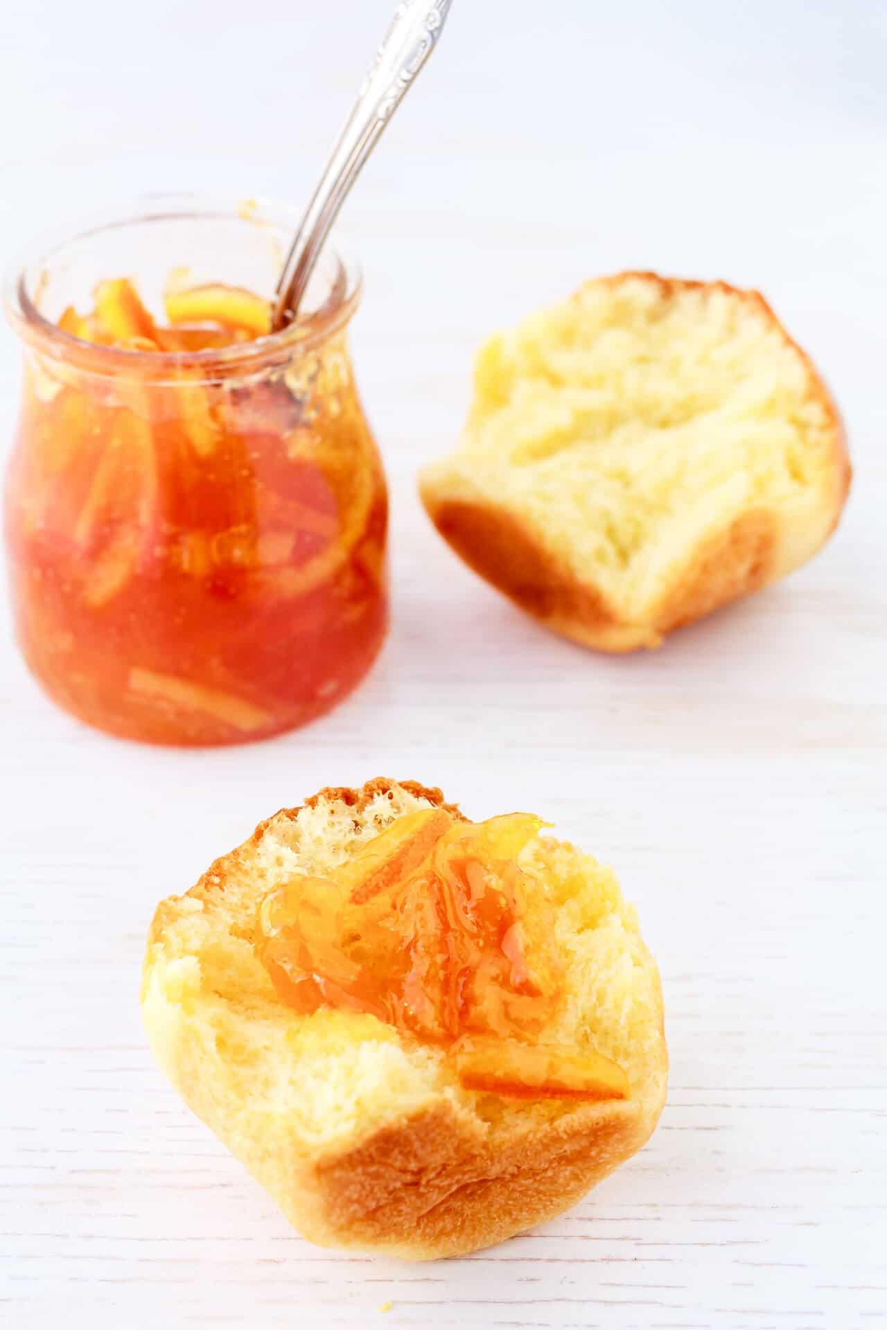 A jar of marmalade served with a brioche bun
