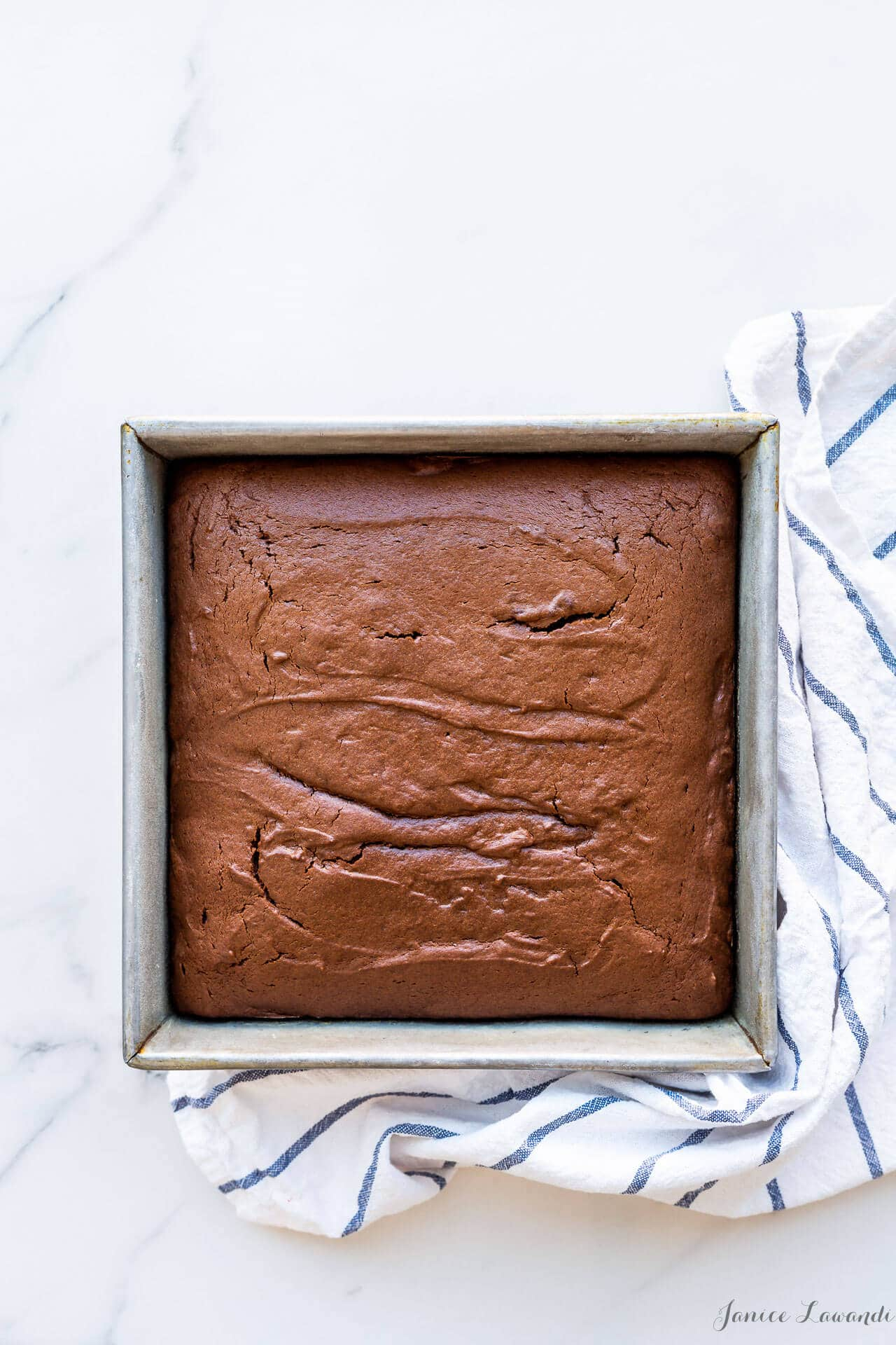 Easy chocolate cake baked in a square 9x9 cake pan, made with melted