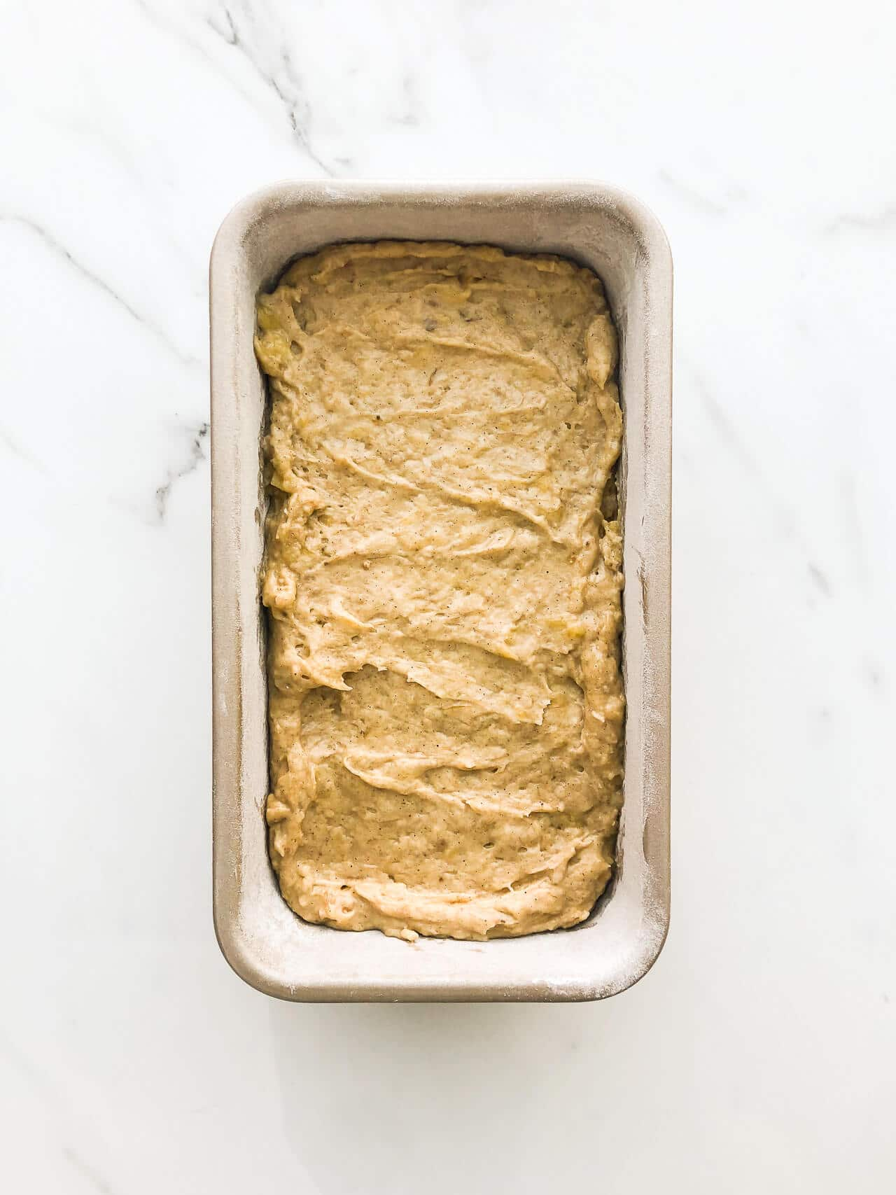 Banana bread batter in a loaf cake pan on marble surface