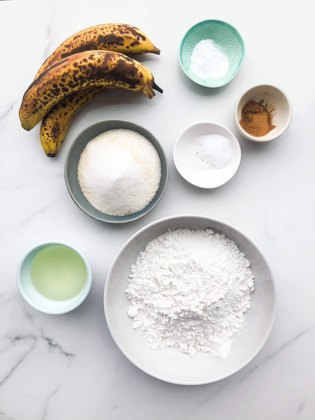 Bowls of ingredients for vegan banana bread (eggless and dairy-free) include oil, bananas, sugar, flour, baking soda, salt, cinnamon