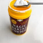 a yellow plastic container of Magic baking powder with 1 teaspoon scooped