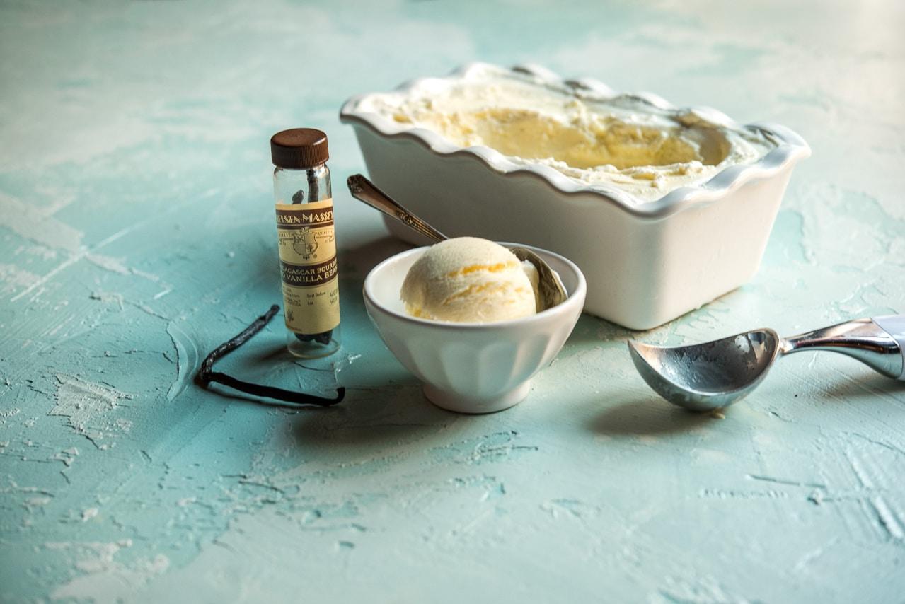 White tub of vanilla bean ice cream served in white bowl next to jar of vanilla beans and ice cream scoop