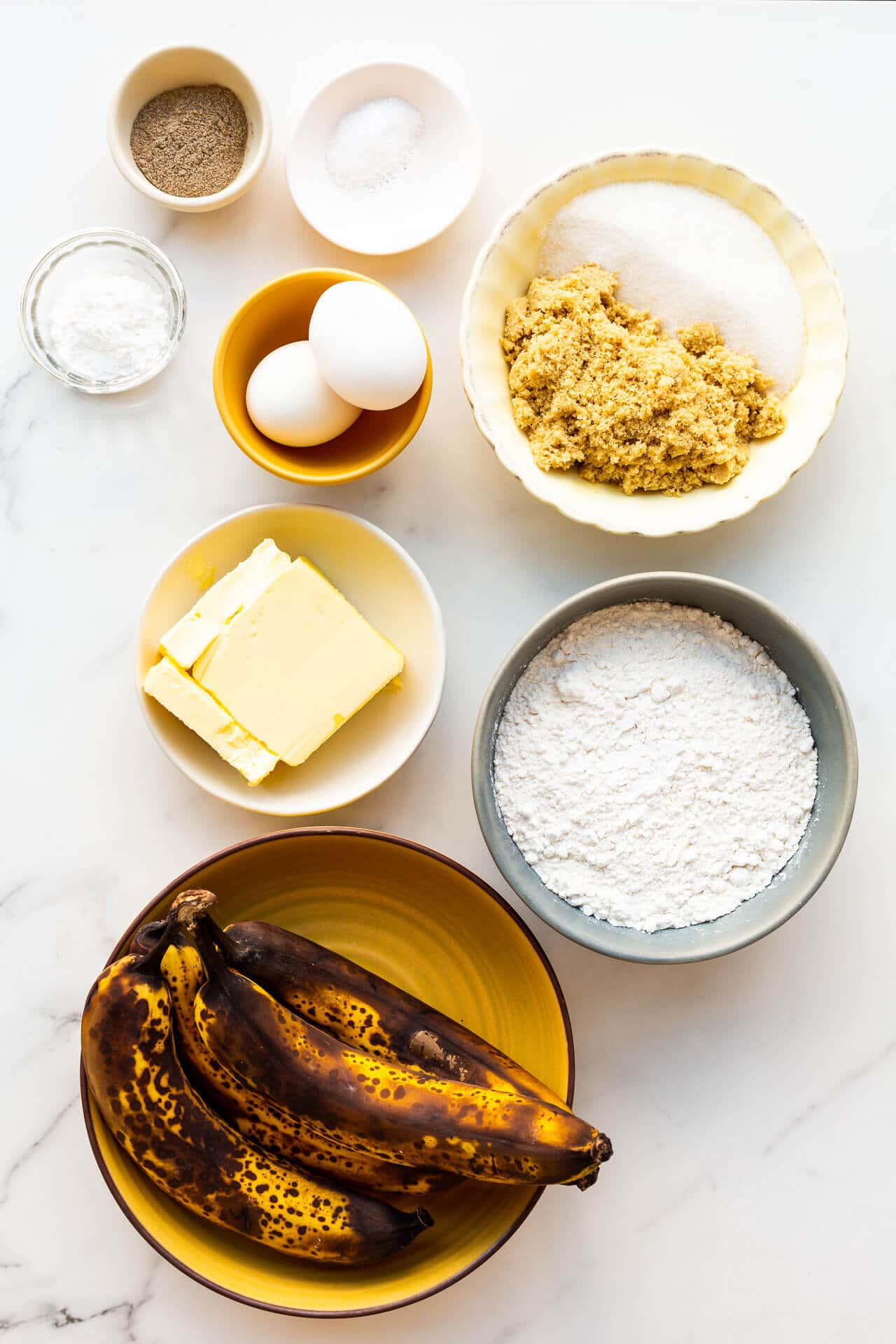 Basic banana bread ingredients: butter, sugar, eggs, bananas, flour, baking powder, and salt (cardamom for flavour)