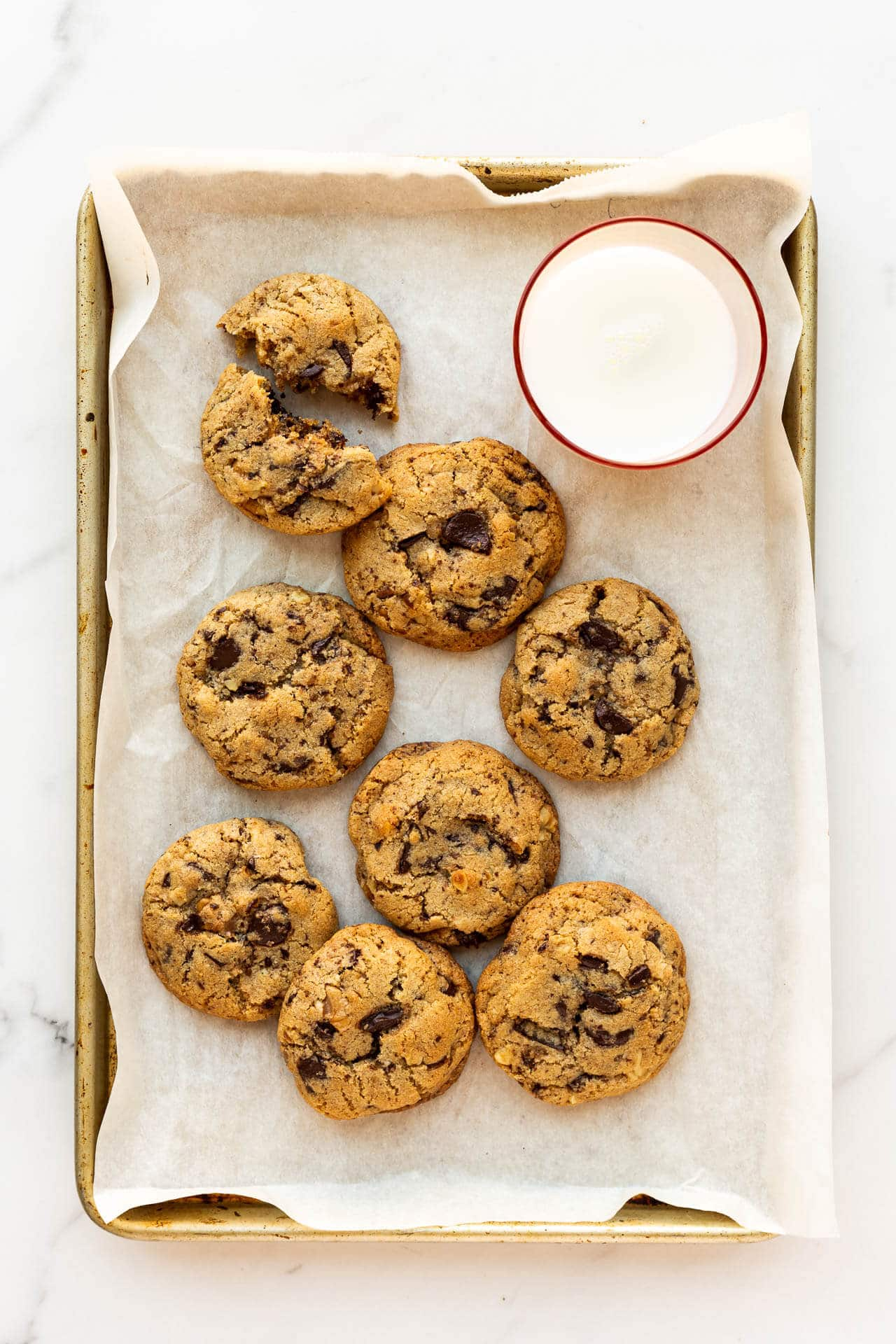 A parchment-lined tray of spelt chocolate chunk cookies with a pink glass of milk