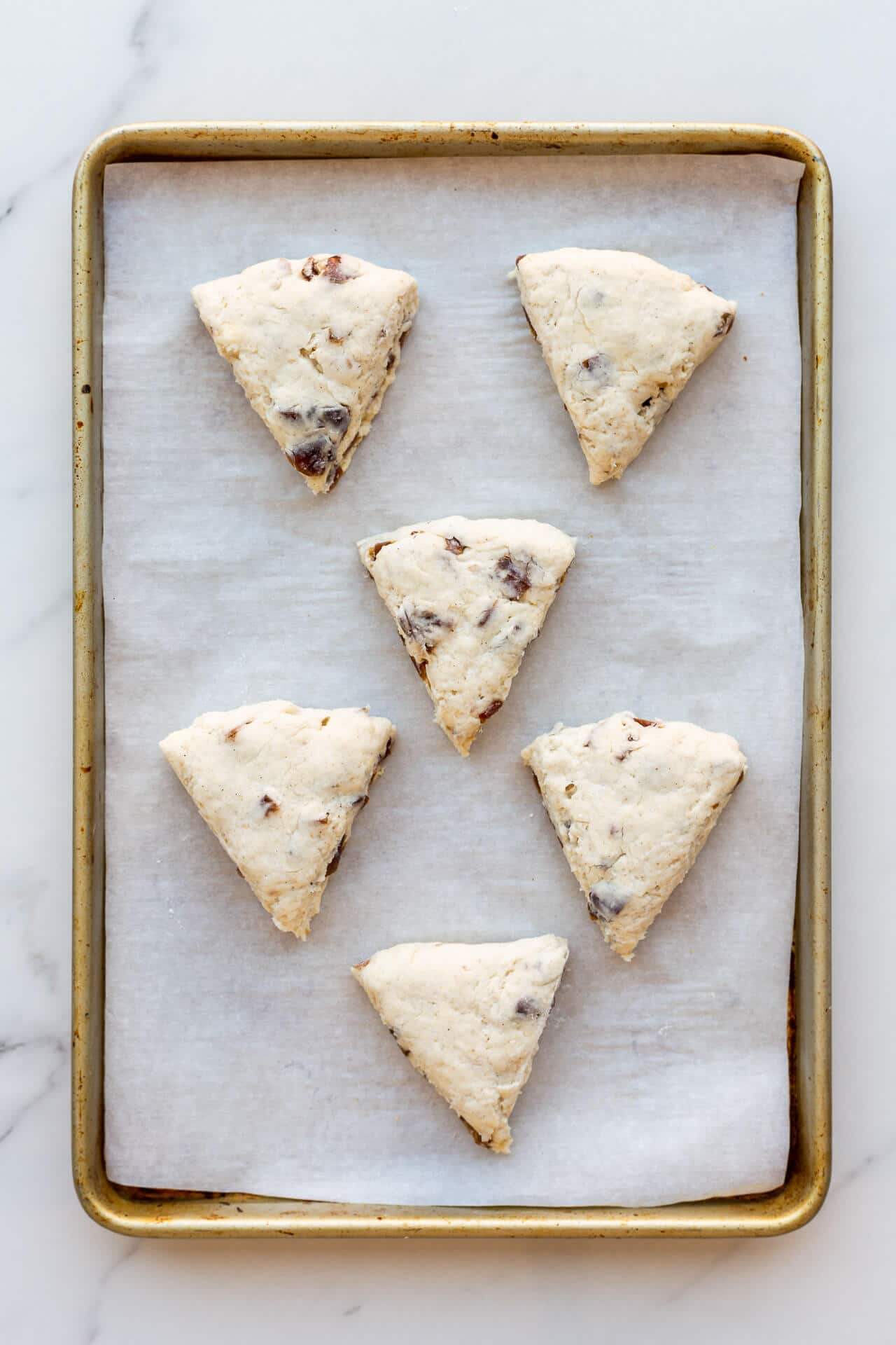 Six (6) triangle wedge scones on a parchment-lined sheet pan before baking