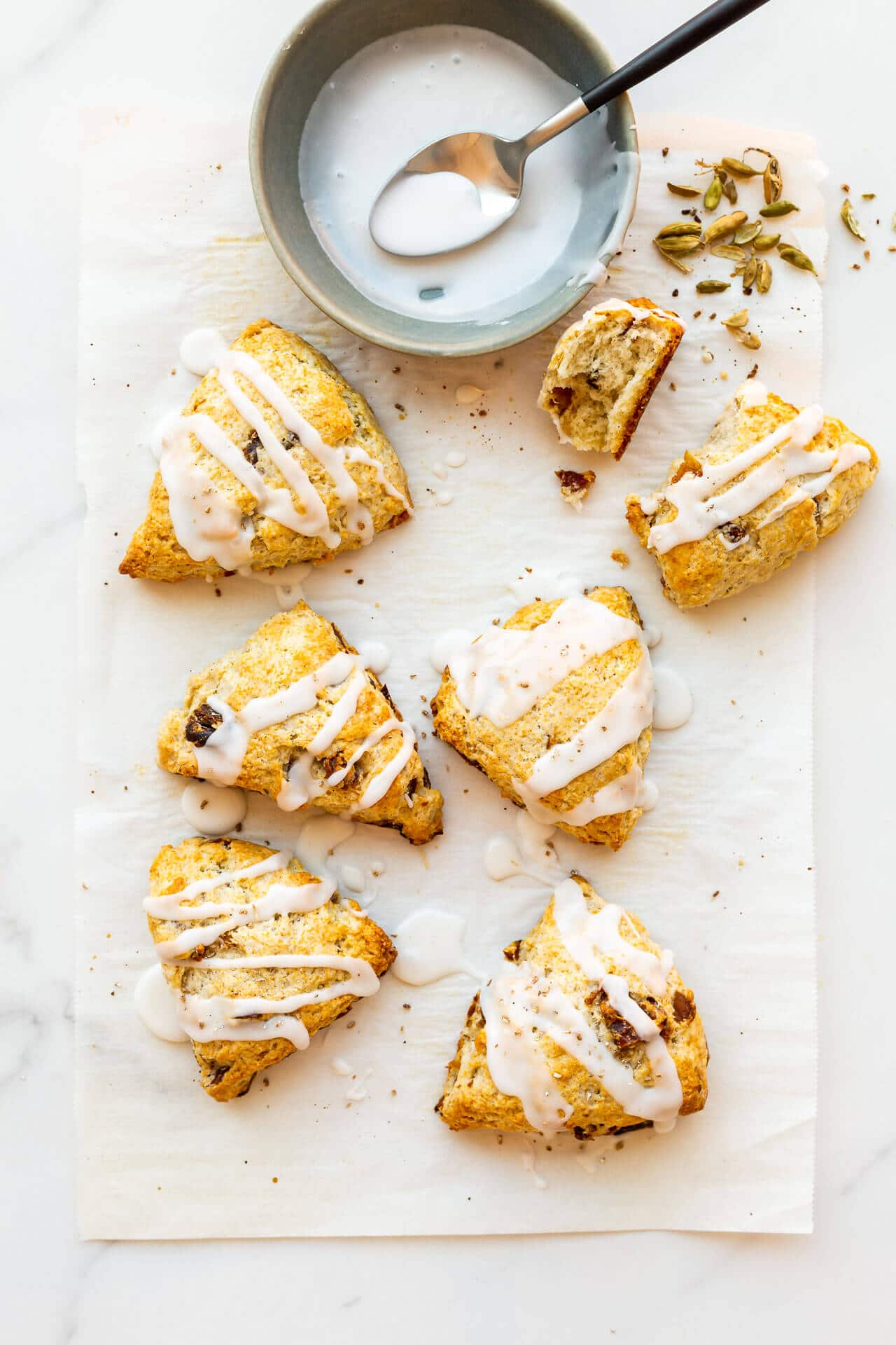 Six (6) glazed fruit scones with icing drizzled on from a bowl with a spoon, sprinkled with freshly ground cardamom from pods