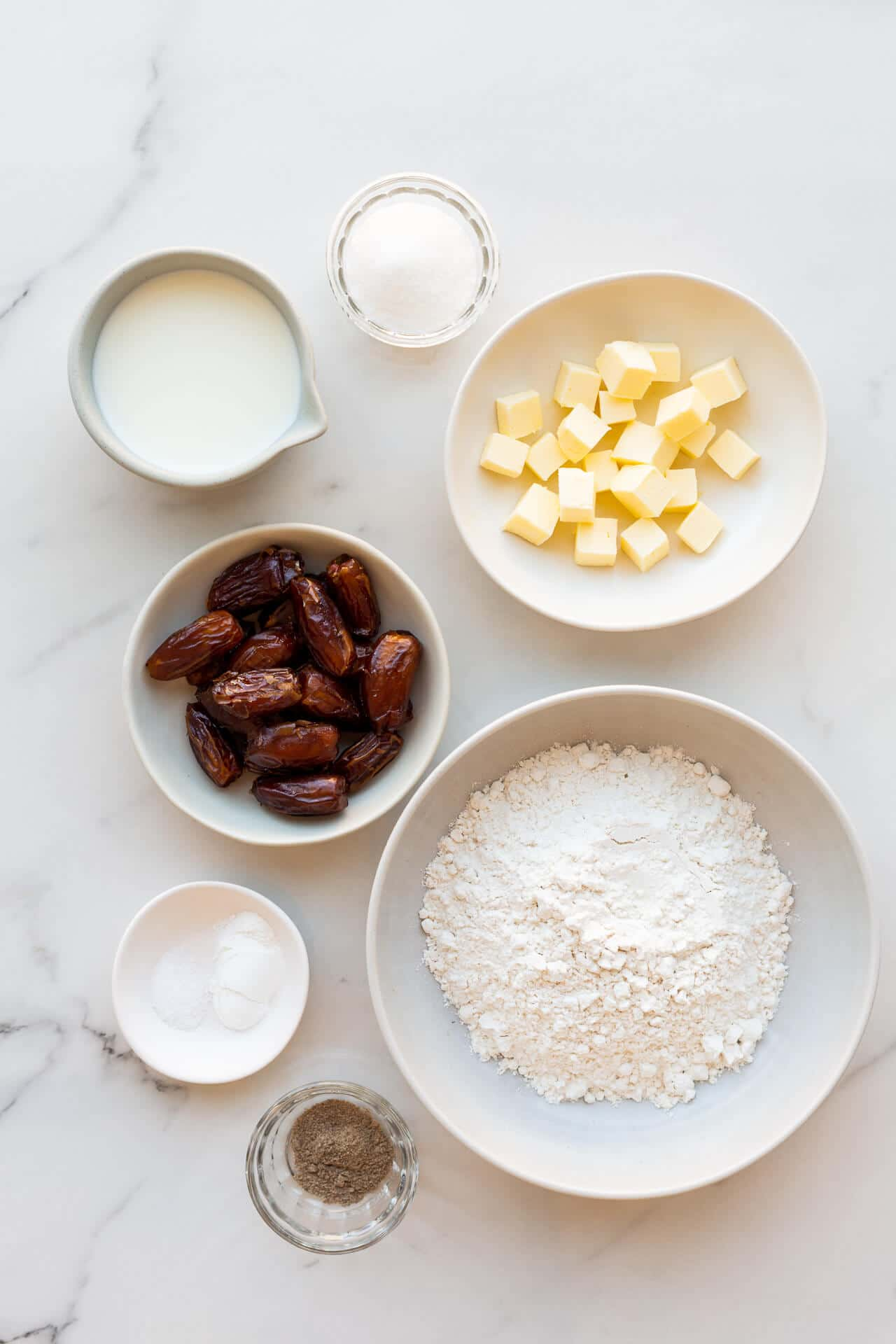 Ingredients to make date scones included cubed butter, salt, baking powder, cream, chopped pitted dates, sugar, flour, and ground cardamom all in bowls for mise-en-place