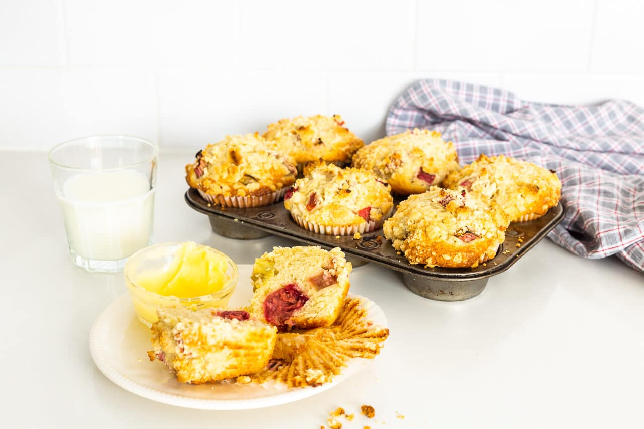 Vintage muffin pan with 6 bakery-style big pink rhubarb muffins with streusel on top, one muffin on a little white plate with a glass of milk and a serving of butter for the muffin