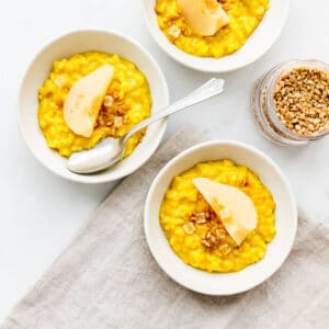 Bowls of homemade rice pudding coloured yellow from turmeric, served with pear slices and maple flakes