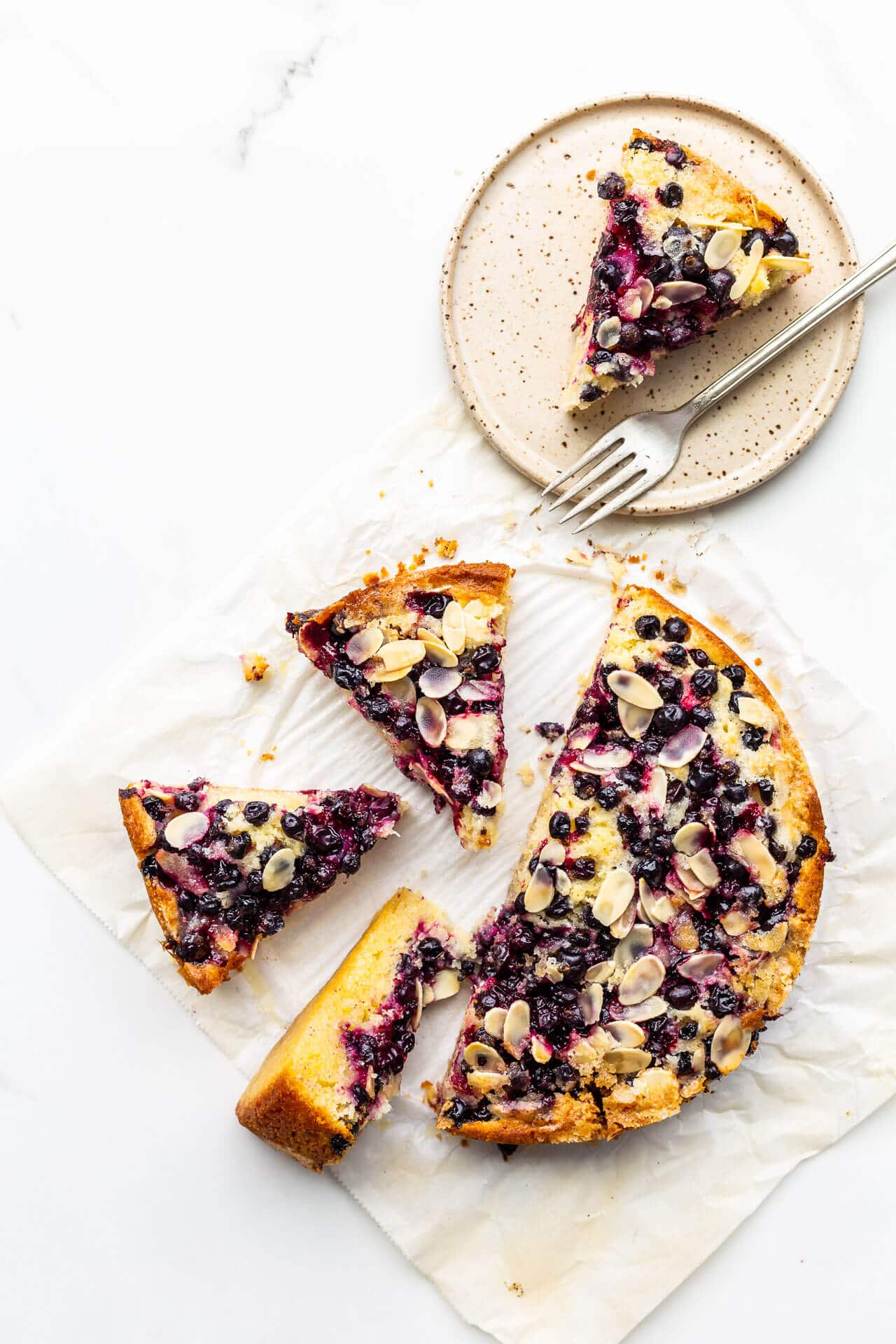 Black currant cake sliced into pieces with one on a speckled ceramic plate with a fork